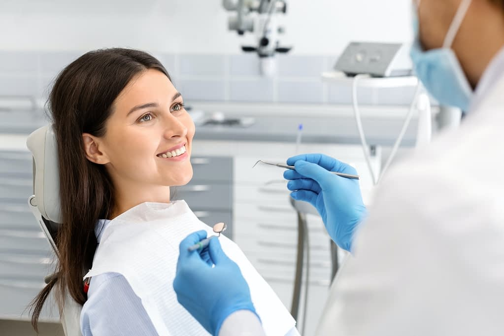 Pretty woman looking at dentist with trust